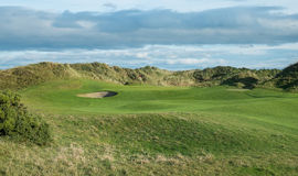 Links golf hole with sand dunes in background. Golf hole on links course viewed from fairway to green with sand dunes in background and rough and gorse in Stock Photos