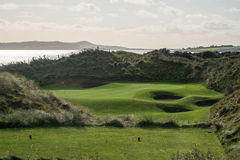 Links par 3 golf hole with large sand dunes and ocean. Links par 3 hole surrounded by large sand dunes with fencing on top and ocean in background and tee box in Stock Image