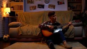 Linksh?ndiger Jugendstudent, der zu Hause die Gitarre sich entspannt nach Vortraghobby spielt lizenzfreie stockbilder