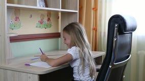 Linkshandige meisjeszitting op stoel door bureaulijst en het schrijven door pen in document notitieboekje Terug naar School Jonge stock footage