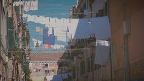 Linne torkas på ett rep i mitt av gatan på en solig dag i Venedig stock video