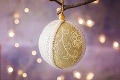 Linnen en kantkerstboombal met ornament het hangen op een tak Gouden slinger schitterend licht op achtergrond De kaart van de gro Stock Fotografie