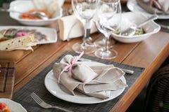 Linnetextil Dekorerad tabell, en platta av den trevligt ordnade servetten, gaffel och kniv Royaltyfri Bild
