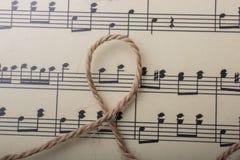 linnetråd som förläggas på papper med musikaliska anmärkningar Fotografering för Bildbyråer