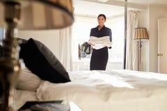 Lino que lleva de la camarera en el dormitorio del hotel, opinión de ángulo bajo Fotos de archivo libres de regalías