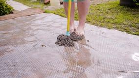Linoléum de essuyage de femme sur le complot après la pluie Linoléum très humide Fin vers le haut banque de vidéos