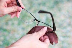 Lins för exponeringsglas för kvinnahand rengörande med suddighetsgräsplanbakgrund arkivbild