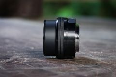 Linse für Kamera, auf einem alten hölzernen Schreibtisch, schwarze Linse, Fotograf stockfoto