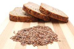 Linseed on cutting board and slices of wholemeal bread Stock Image