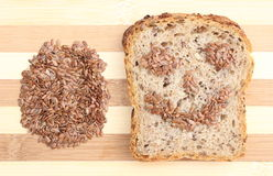 Linseed on cutting board and slices of wholemeal bread Royalty Free Stock Photos