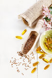 Linseed and flaxseed oil capsules over white background Stock Image