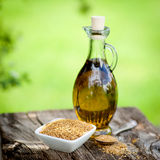 Linseed oil. And linseed on wooden ground Royalty Free Stock Image