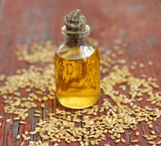 Linseed oil in bottle on wooden background Royalty Free Stock Image