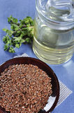 Linseed oil and flax seeds. On ceramic plate closeup. Small shallow DOF Royalty Free Stock Photo