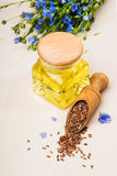 Linseed oil, flax seeds, and flowers on a light background. Stock Photos