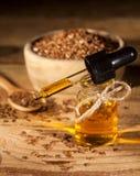 Linseed olej, łyżka i puchar linseeds na drewnianym tle, Zdjęcie Stock