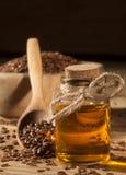 Linseed olej i puchar linseeds na drewnianym tle Obraz Stock