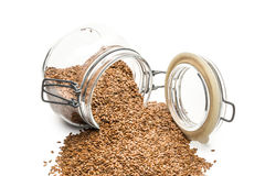 Linseed in an overturned glass jar Royalty Free Stock Photography