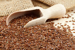 Linseed with wooden scoop. Linseed, flax seeds, wooden scoop, sacking bag Royalty Free Stock Photography