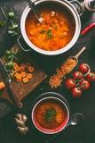 Linssoppa i kruka och bunke med skeden och sleven Laga mat ingredienser på mörk lantlig köksbordbakgrund, bästa sikt Sunt royaltyfria bilder