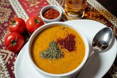 Linssoppa med kryddor i en vit bunke med en sked på en vit platta På tabellen med en bordduk med nationella modeller royaltyfri foto