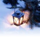 Linterna ardiente en la nieve Foto de archivo libre de regalías