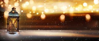 Linterna ardiente en nieve con el bokeh de oro Imágenes de archivo libres de regalías