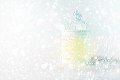 Linterna blanca con la luz caliente entre los copos de nieve Imagen de archivo libre de regalías