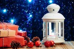 Linterna blanca con una vela ardiente y cajas con los regalos en el fondo del árbol de navidad con las luces Hermoso fotografía de archivo libre de regalías