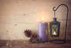 Linterna blanca del vintage con las velas ardientes, los conos del pino en la tabla de madera y el fondo de las luces del brillo  Fotografía de archivo