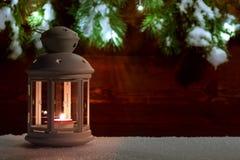 Linterna con una vela ardiente en la nieve contra la perspectiva de una pared de madera vieja adornada con el árbol de navidad fotos de archivo libres de regalías
