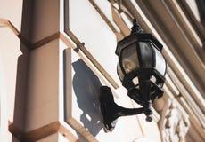 Linterna de cristal vieja en un marco torcido negro en la pared blanca del edificio de la ciudad Lámpara de pared en un día solea fotos de archivo