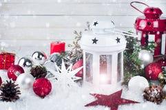 Linterna de Cristmas con las decoraciones y la nieve Foto de archivo