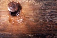 Linterna de keroseno oxidada vieja en piso de madera Imagen de archivo libre de regalías