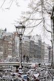 Linterna de la ciudad con muchas bicis en nieve en invierno en Amsterdam fotografía de archivo