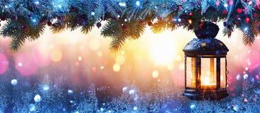 Linterna de la Navidad en nieve con la rama del abeto en la luz del sol imagenes de archivo