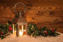 Linterna de la Navidad en nieve y acebo Imagen de archivo