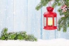 Linterna de la vela de la Navidad en rama de árbol de abeto en nieve Foto de archivo