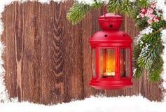 Linterna de la vela de la Navidad en rama de árbol de abeto en nieve Fotografía de archivo