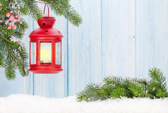 Linterna de la vela de la Navidad en rama de árbol de abeto en nieve Fotos de archivo