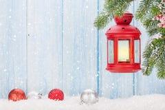 Linterna de la vela de la Navidad en rama de árbol de abeto en nieve Imagenes de archivo