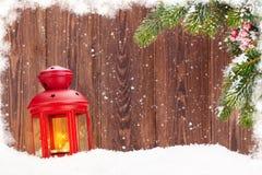 Linterna de la vela de la Navidad y rama de árbol de abeto en nieve Fotos de archivo libres de regalías