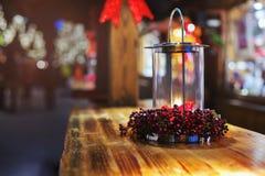 Linterna de la vela que brilla intensamente en la tabla en el mercado de la Navidad por la tarde Iluminado con la luz Foto de archivo