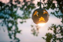 Linterna del árbol de coco con la lámpara en el fondo de la puesta del sol en la playa Imagen de archivo