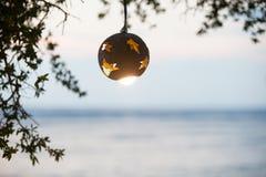 Linterna del árbol de coco con la lámpara en el fondo de la puesta del sol en la playa Foto de archivo