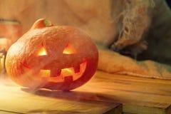 Linterna del enchufe de la cabeza de la calabaza de Halloween en fondo de madera Imagenes de archivo