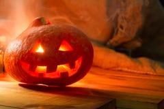 Linterna del enchufe de la cabeza de la calabaza de Halloween en fondo de madera Foto de archivo