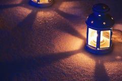 Linterna dos con la vela ardiente en nieve por la tarde Fotografía de archivo