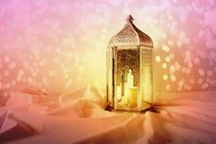 Linterna marroquí, árabe de plata ornamental en el tiro de lino Vela ardiente, luces coloridas del bokeh que brillan saludo imágenes de archivo libres de regalías