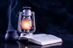 Linterna negra del humo y del gas del pote de la bruja y libro abierto en fondo oscuro y de niebla fotografía de archivo libre de regalías